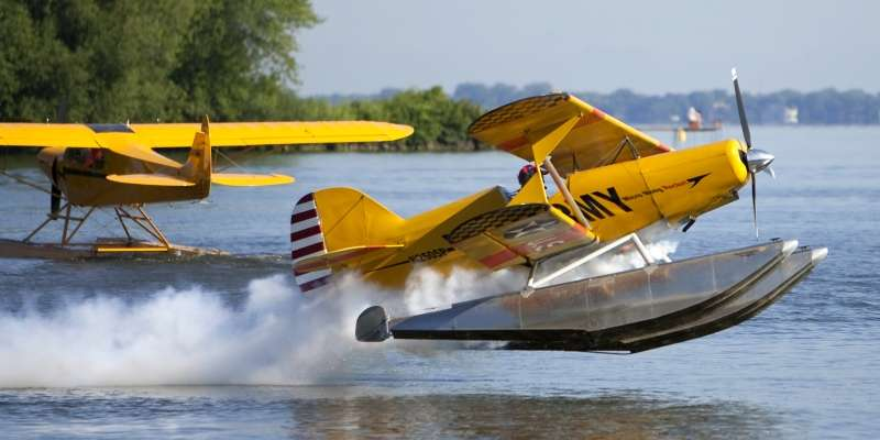 A plane takes off from the tranquil waters of the Oshkosh Seaplane Base.