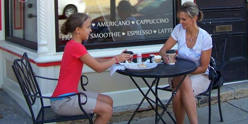 A mom and daughter enjoy a quiet moment of fun together over coffee.