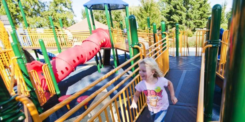 A young girl enjoys running around the equipment at the KASH playground. Photo: KT Elements