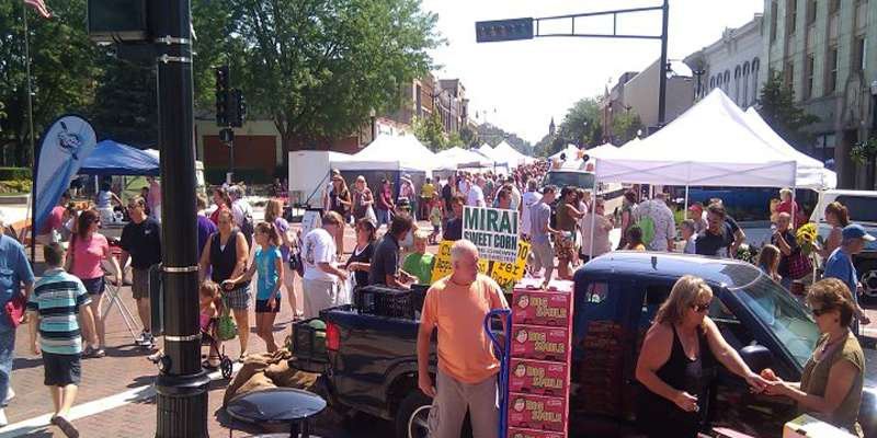 Visitors explore the tents full of fresh produce and other local goods available at the farmer's market.