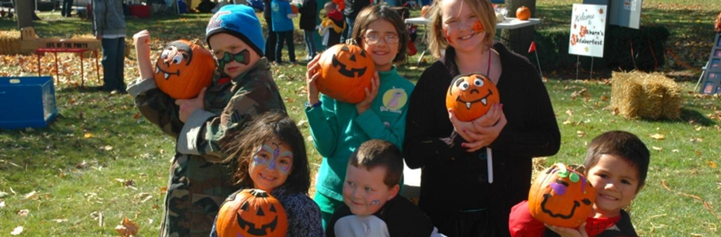 Kids take a pause from the fun to show off their painted faces and pumpkins.