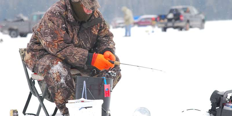An ice fisherman bundles up and waits for a bite.