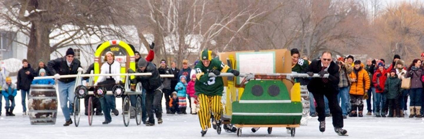 Participants decked out in whacky costumes compete in the bed races during the annual Winter Festival.