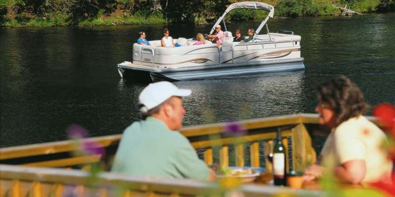 Boaters cruise Eagle River's Chain of Lakes in their pontoon while diners enjoy a meal on an outdoor patio.