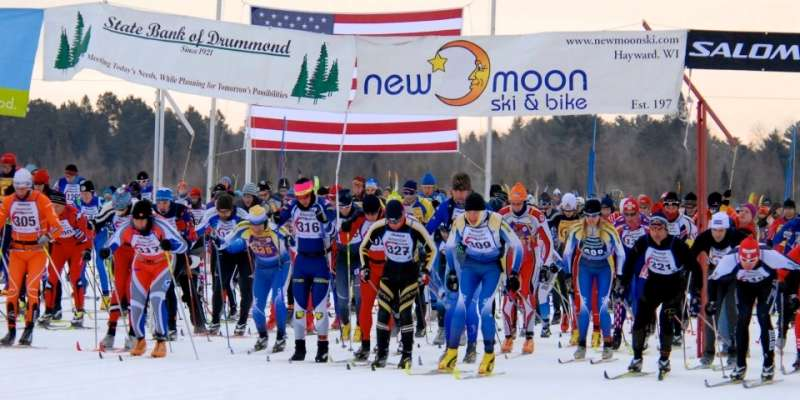Hundreds of skiers take off from the starting line.
