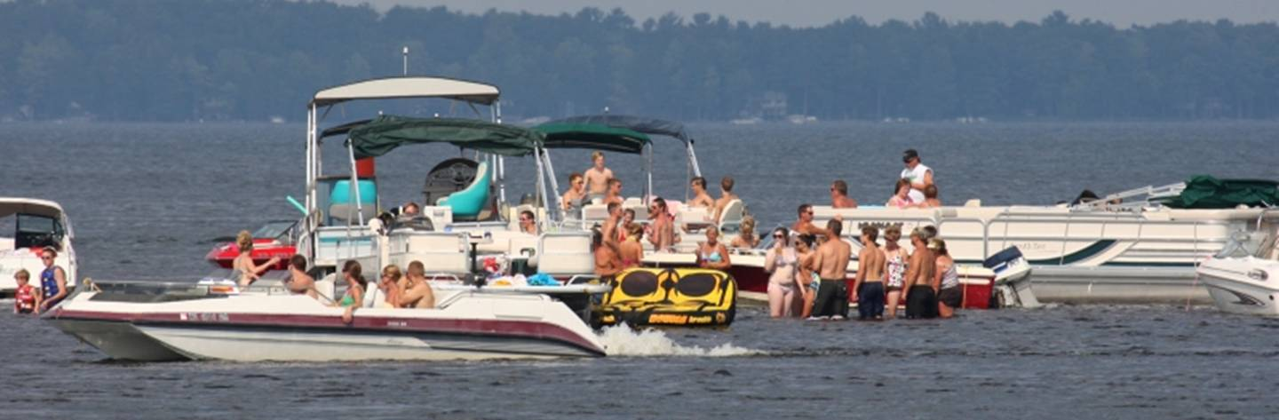 Boaters gather at a sand bar for summertime fun in Shawano Lake.