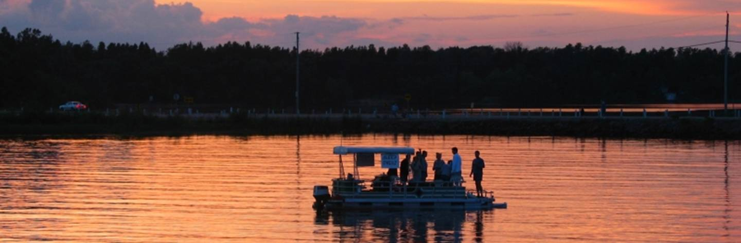 A group of friends floats on a pontoon at dusk.