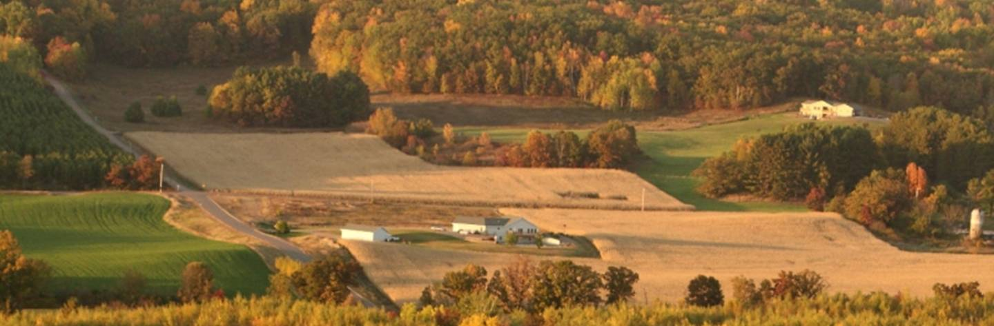 An aerial photo captures a farm surrounded by rolling hills and plush forest. Photo by Tina Lockbaum.