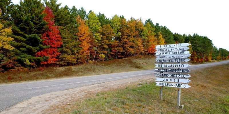 A sign directs travelers to area businesses with a rainbow of fall colors in the background.