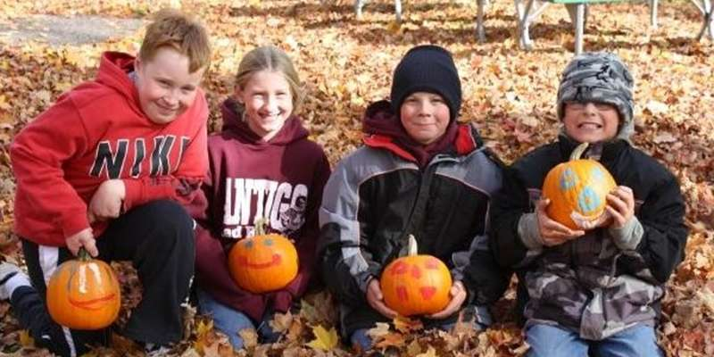 Kids enjoy the fall tradition of decorating pumpkins.