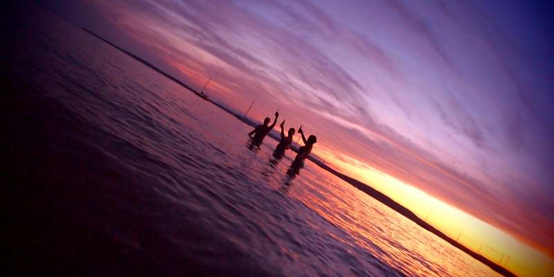A group of friends make a toast at dusk while wading in the waters of Lake Superior.