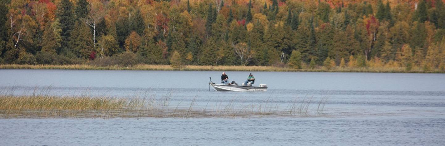 Fishermen troll Langlade County Lake in the fall as the beautiful leaves along the banks change color.