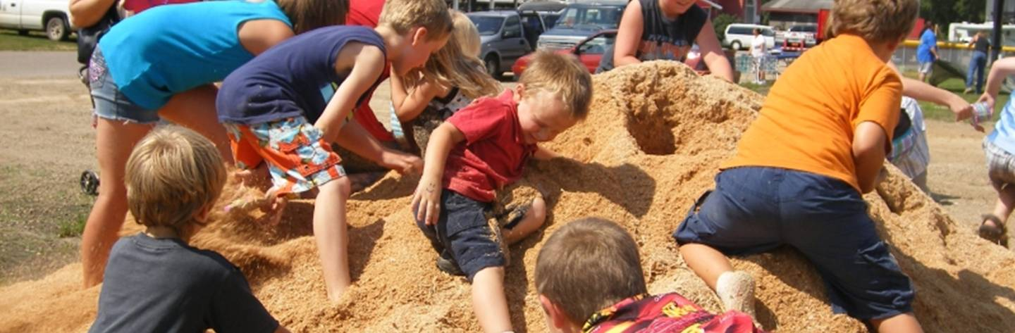 Kids dig into a sand pile at the Poker Run.