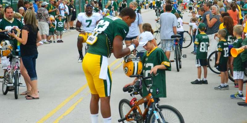 Kids line up for the opportunity to have their favorite player ride their bike and sign an autograph.