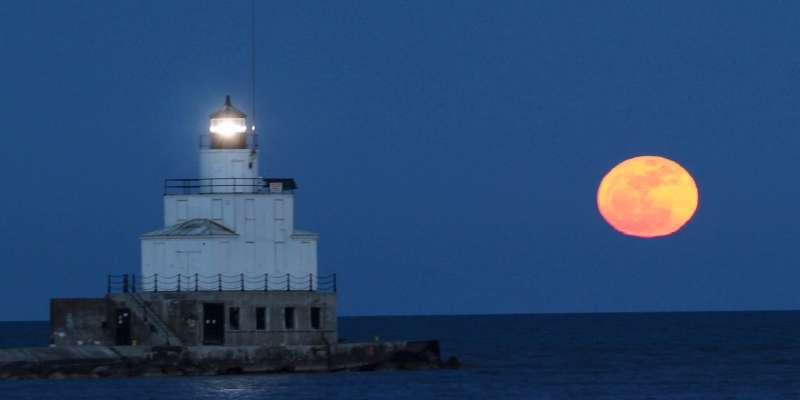 A spectacular full moon glows in the sky above Lake Michigan.