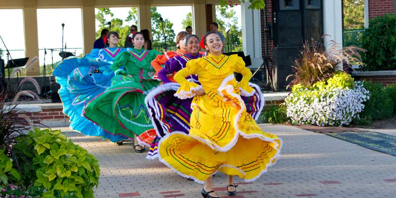 Performers dressed in beautiful costumes perform at the Juntos Celebramos en el River Front.