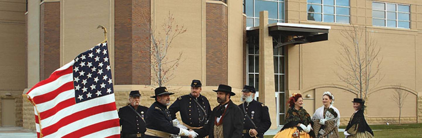 Actors dressed in period costumes stand in front of the Civil War Museum.