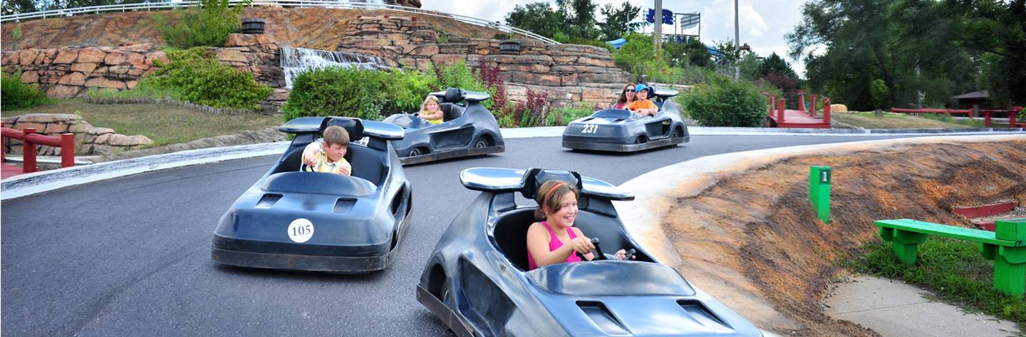 Kids put the pedal to the metal as they race around the go-kart track.