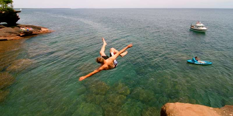 A brave jumper does a flip into the crystal clear water.