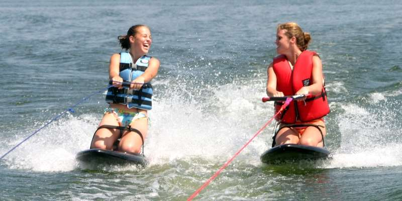 Friends enjoy speeding across the lake side by side on their kneeboards.