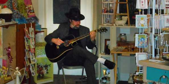 A musician plays in a downtown boutique during Spring Gallery Night.