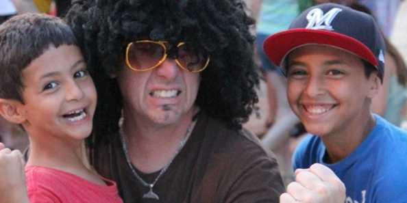 A groovy member of The Boogie Men has some fun with concert-goers at a 2014 summer concert.