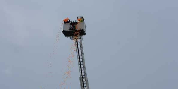 "The ""snowballs"" fall from the top of the ladder truck for the Snowball Drop"