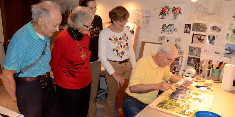 Visitors watch participating artist at work.