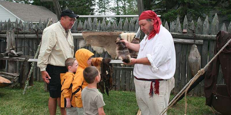 A fur trade re-enactor discusses fur trade traditions with a young family