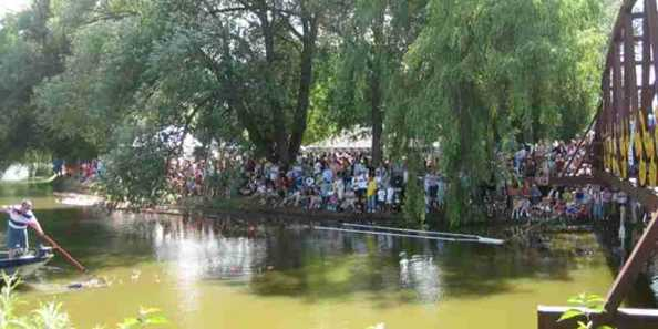 Event Goers Line the River Banks During the Duck Race