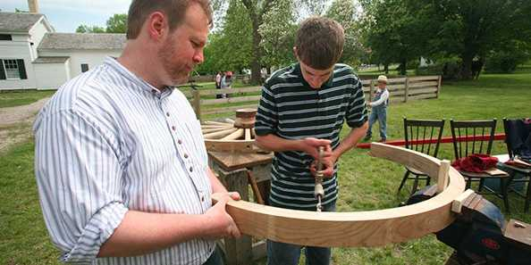 A wheelwright demonstrates his craft at Wade House