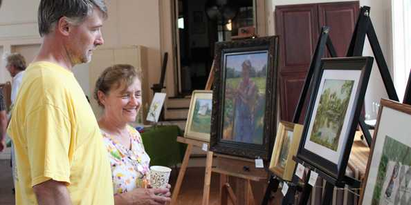 Patrons admire the pretty results of the Theodore Robinson Plein Air Painting Contest, hosted in Evansville.
