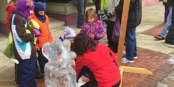 Passersby check out an ice carving artist at work during Chili Fest.