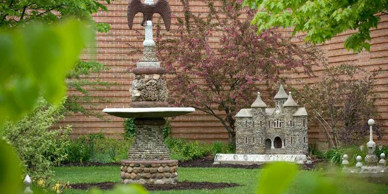 Whimsical miniature castles and other creations grace the Carl Peterson sculpture garden.