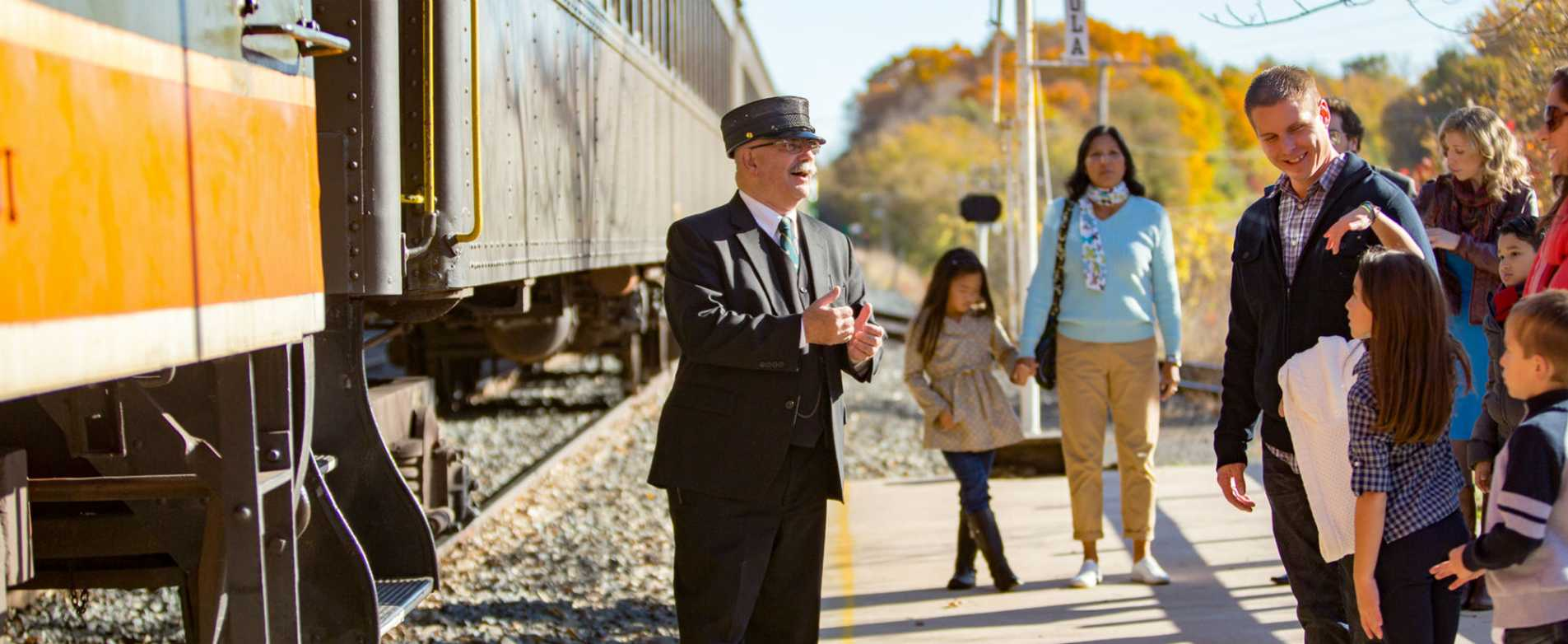 Train Conductor Gretting Families Outside Train