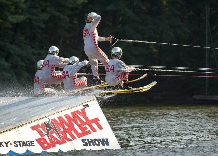 Performance water-skiers flying off of jump