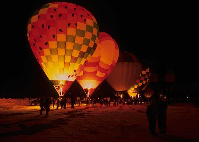 Colored hot air balloons stand in the night