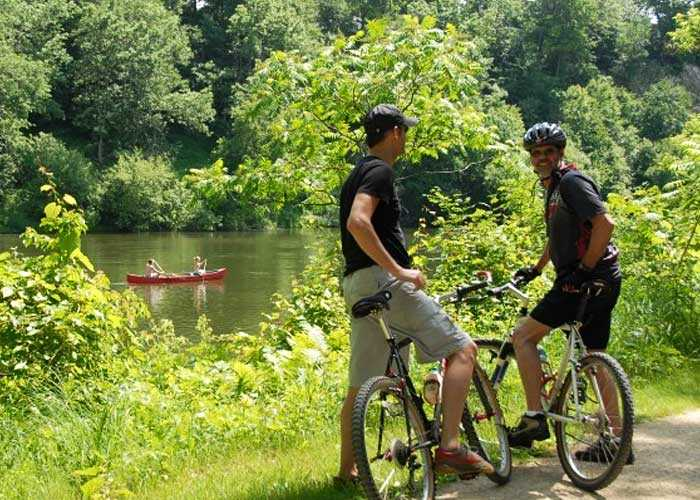 Two guys rest on their bikes near a river