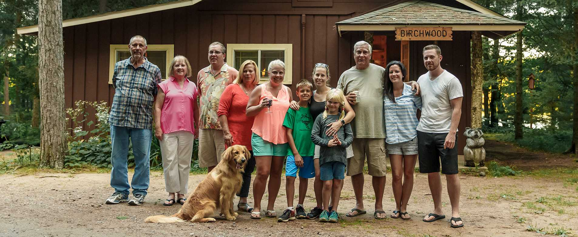 Family Standing in Front of Birchwood Cabin at Black's Cliff Resort