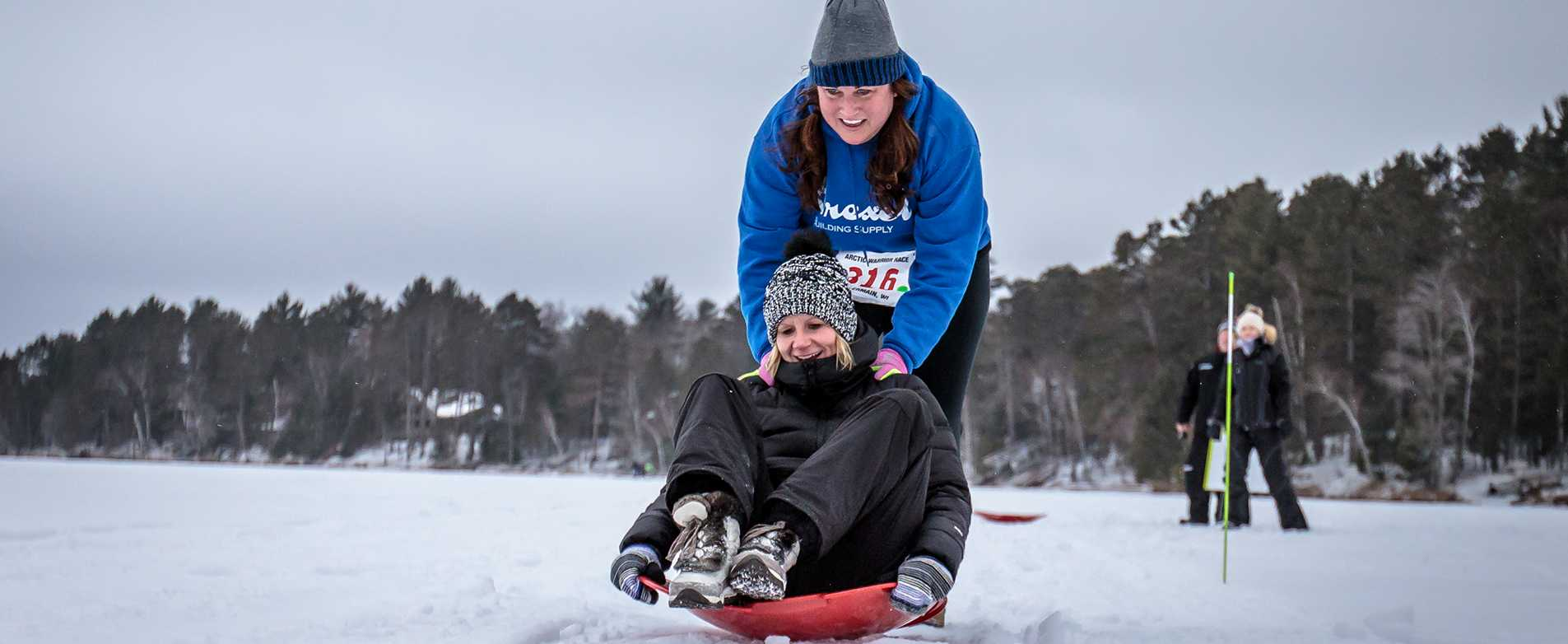 Woman pushing friend on sled