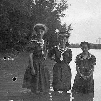 old photo of three girls standing in lake