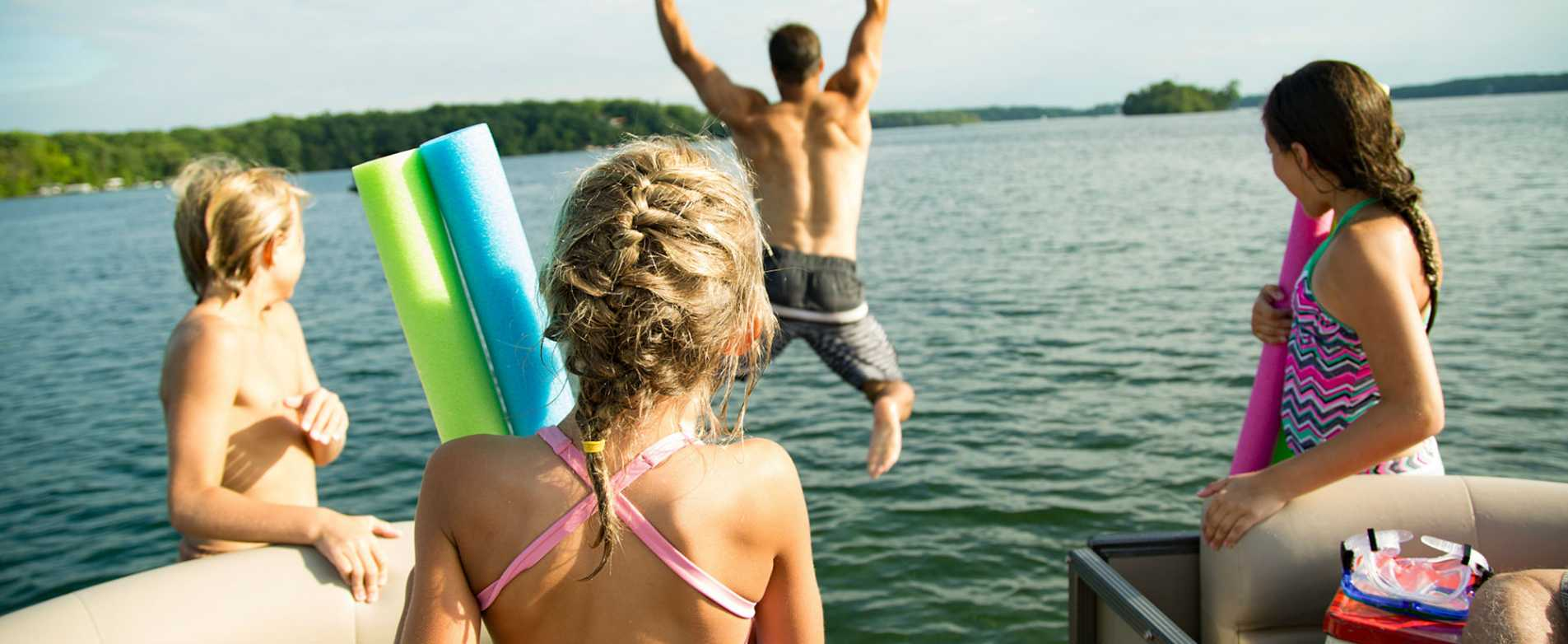 Dad Jumping off Pontoon Boat While Daughters Watch