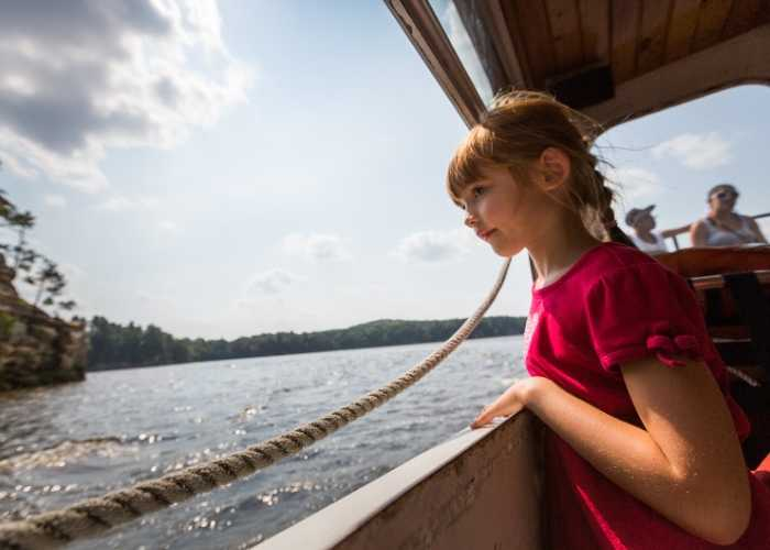 young girl on boat looks overboard
