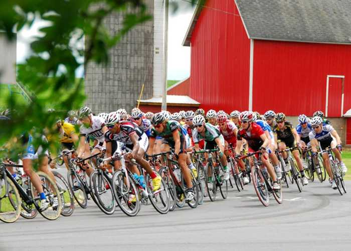 Bike race past a farm