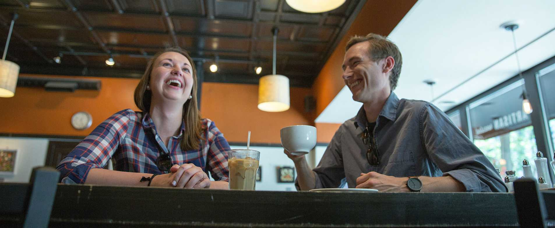 Couple Laughing Over Coffee at Ancora Coffee Shop