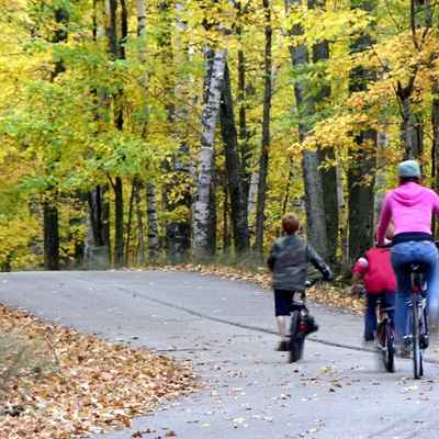 Mom and kids biking along a paved path.