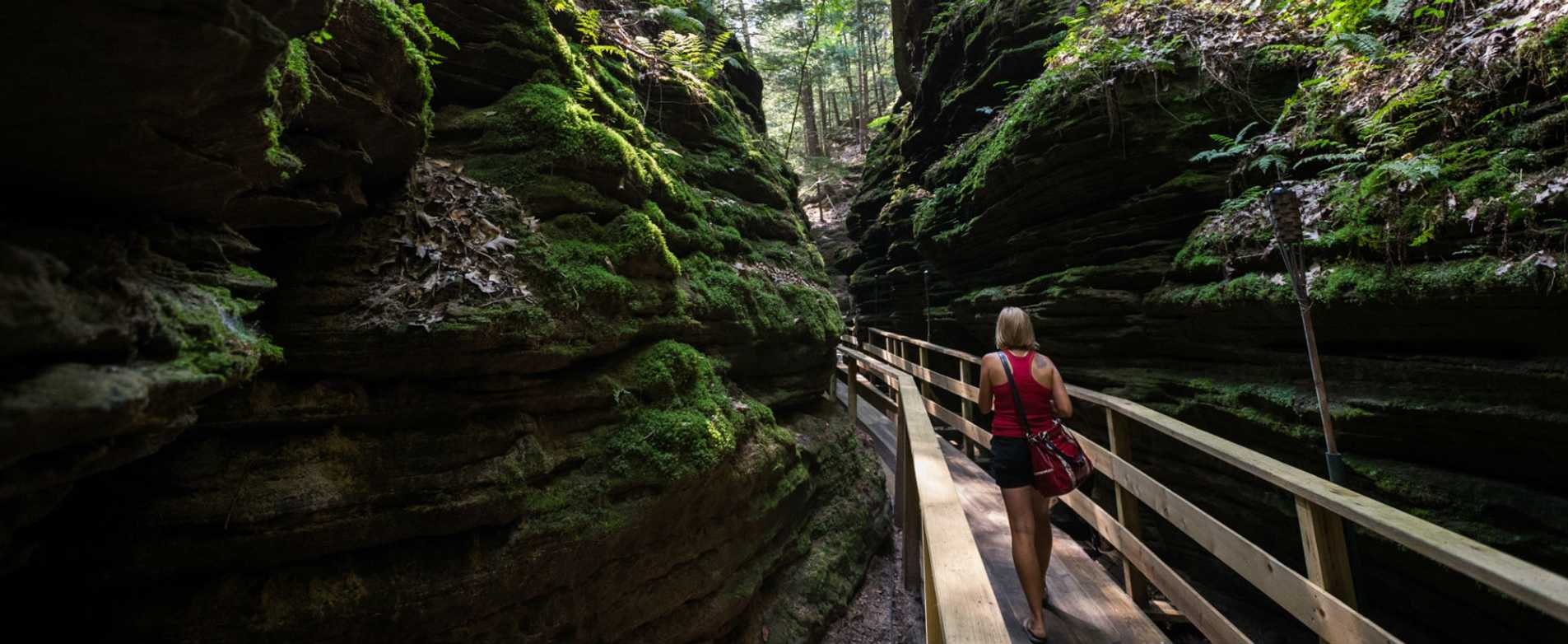 Woman Walking Across Bridge in Dells Canyon