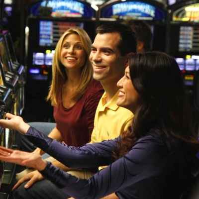 man and two women playing slot machines