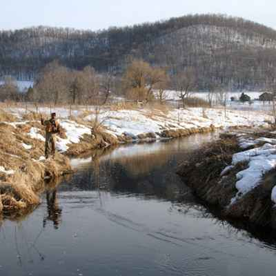 man fishing during winter in river