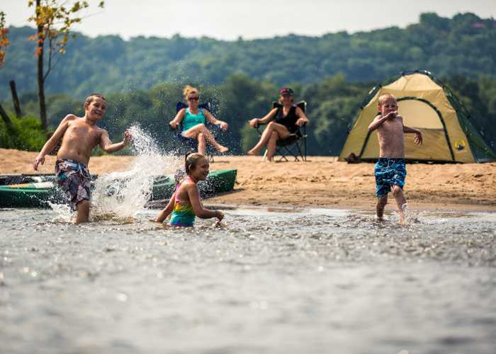 Kids running into river at sandy campsite